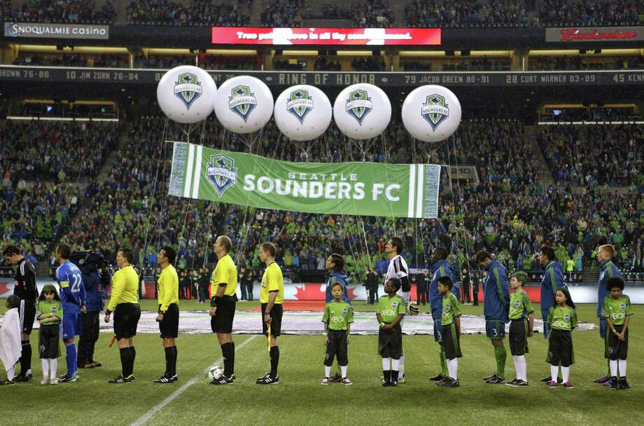 Seattle Sounders and Montreal Impact players listen to the National Anthem during the Sounders season opener. Photo: JOSHUA TRUJILLO / SEATTLEPI.COM
