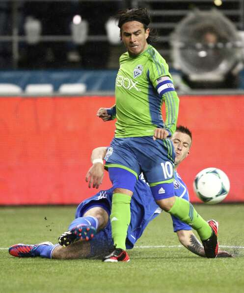 Seattle Sounders player Mauro Rosales and Montreal Impact player Jeb Brovsky battle for control of t