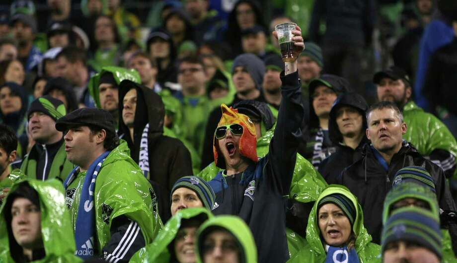 A Seattle Sounders fan raises his beer during the season opening match against the Montreal Impact. Photo: JOSHUA TRUJILLO / SEATTLEPI.COM