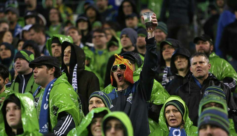 A Seattle Sounders fan raises his beer during the season opening match against the Montreal Impact.