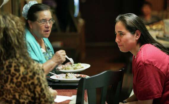 Anna Vasquez talks with mother Maria Vasquez, center, and friend Denise Tristan, left, as they celebrate Thanksgiving with family members at her mother's house, her first after being released on parole, Thursday, Nov. 22, 2012. The children in family  aren't allowed to be at family gatherings with Anna present. Photo: Bob Owen, San Antonio Express-News / © 2012 San Antonio Express-News