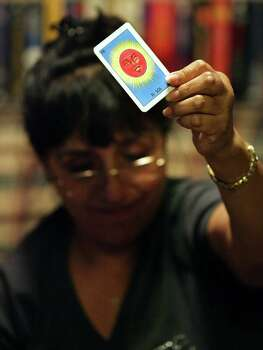 Margaret Vasquez, Anna Vasquez's sister-in-law, holds up a loteria card, as the family plays the family favorite tradition, celebrating Thanksgiving with family members at Anna's mother's house, her first after being released on parole, Thursday, Nov. 22, 2012. Photo: Bob Owen, San Antonio Express-News / © 2012 San Antonio Express-News