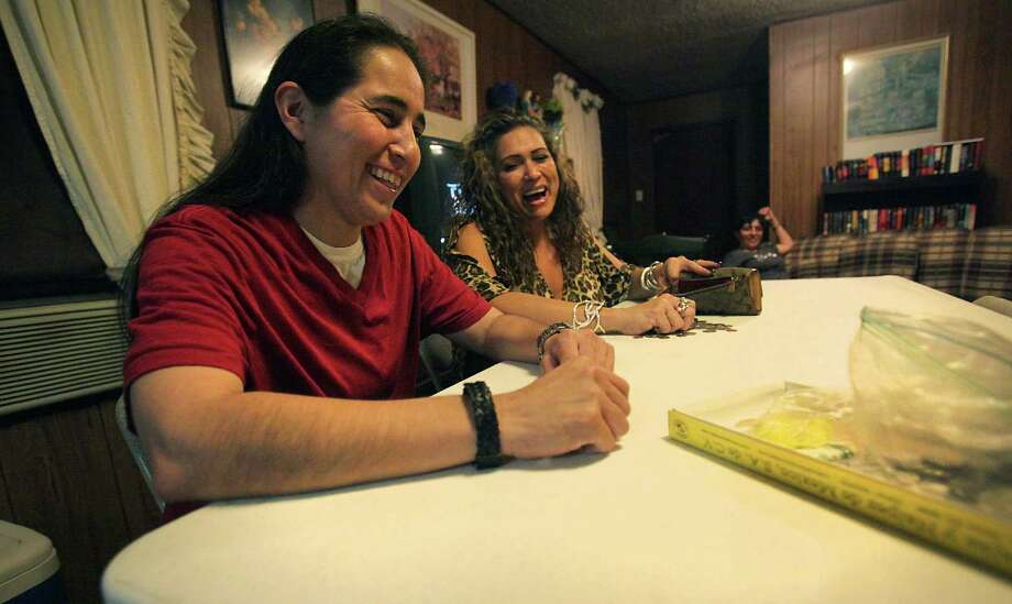 Anna Vasquez, left, sits next to long time friend Denise Tristan as the family prepares to play a game of loteria, a traditional Mexican game.   Thursday, Nov. 22, 2012. Photo: Bob Owen, San Antonio Express-News / © 2012 San Antonio Express-News
