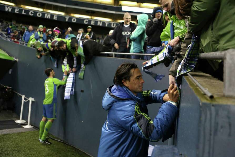 Seattle Sounders players Mauro Rosales and Brad Evans sign autographs during the Sounders season ope