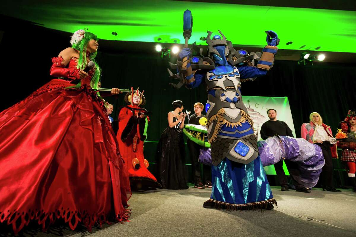 Brian Morris, right, dressed as the Draena Shaman from World of Warcraft, celebrates his first place victory during masters bracket of the costume competition on the second day of the annual Emerald City Comicon on Saturday, March 2, 2013, in the Washington State Convention Center in Seattle, Wash. Morris walked away with 1000 dollars in prize money.