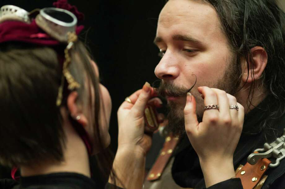 "Jesse Lagers, right, dressed as a ""steamtrooper,"" gets his mustache touched up by his girlfriend Torri Hokanson, left, on the second day of the annual Emerald City Comicon on Saturday, March 2, 2013, in the Washington State Convention Center in Seattle, Wash. Photo: JORDAN STEAD / SEATTLEPI.COM"