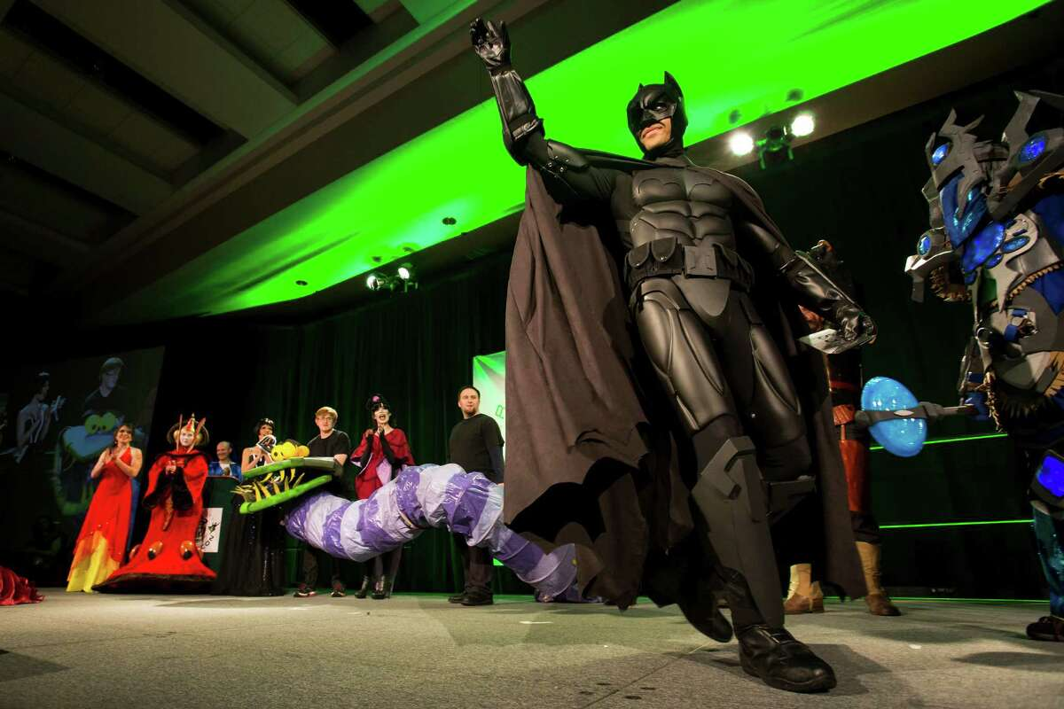 Brandon Nicholas, right, dressed as Batman, leaves the stage after receiving third place in a costume competition on the second day of the annual Emerald City Comicon on Saturday, March 2, 2013, in the Washington State Convention Center in Seattle, Wash.