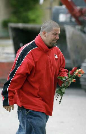 Jeremy Bush carries flowers to a home over a huge sinkhole that swallowed his brother Jeffrey late Thursday in Seffner, Fla., Sunday, March 3, 2013. Crews are set to begin the demolition of the Florida home on Sunday, after search personnel failed to find Jeffrey Bush. (AP Photo/Chris O'Meara) Photo: Chris O'Meara