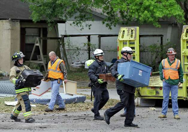 Hillsborough County, Fla., firefighters remove salvaged items, from the home where a sinkhole swallowed Jeffrey Bush, late Thursday in Seffner, Fla., on Sunday, March 3, 2013. Crews are set to begin the demolition of the home on Sunday, after search personnel failed to find Bush. (AP Photo/Chris O'Meara) Photo: Chris O'Meara