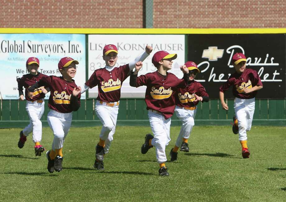 Sun Devils (Texas League division) team members run out onto the field during Bellaire Little League Opening Day Ceremony at Jessamine Field on March 2. Photo by Thomas Nguyen. Photo: Thomas Nguyen, For The Chronicle / Freelance
