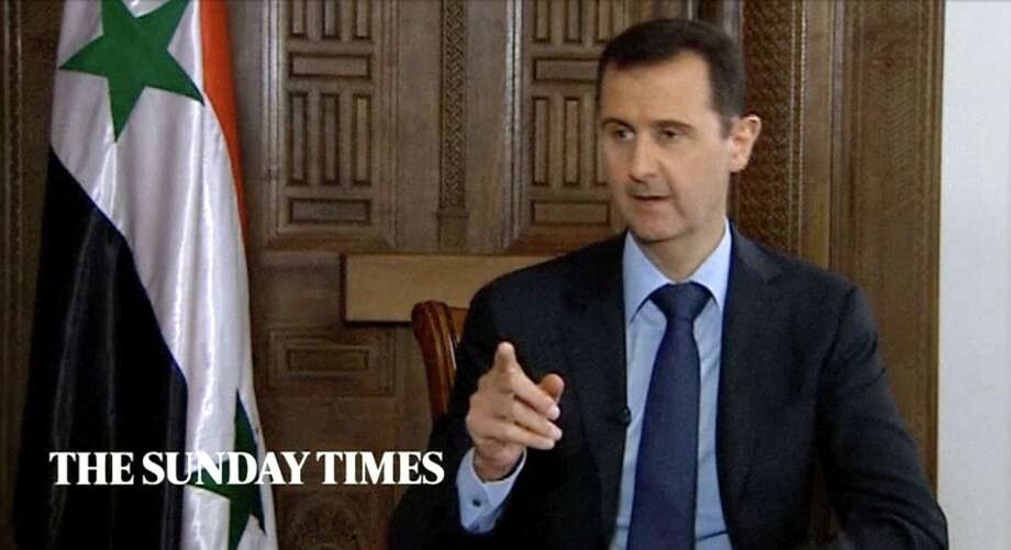 "In this image taken from video filmed on Thursday, Feb. 28, 2013 and released Saturday evening, March 2, 2013, Syrian President Bashar Assad gestures while speaking during an interview with the Sunday Times, in Damascus, Syria. Iran and Syria condemned a U.S. plan to assist rebels fighting to topple Assad on Saturday and signaled the Syrian leader intends to stay in power at least until 2014 presidential elections. Assad told the Sunday Times in the interview timed to coincide with U.S. Secretary of State John Kerry's first foreign trip that ""the intelligence, communication and financial assistance being provided is very lethal."" Kerry announced on Thursday that the Obama administration was giving an additional $60 million in assistance to Syria's political opposition and would, for the first time, provide non-lethal aid directly to the rebels.  (AP Photo/Sunday Times via AP video)  Photo: AP"