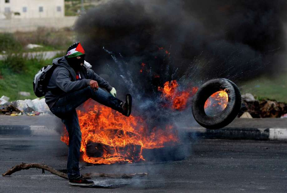 A masked Palestinian stone thrower kicks a burning tire during a protest to support of Palestinian prisoners, outside Ofer, an Israeli military prison near the West Bank city of Ramallah, Thursday. Photo: AP