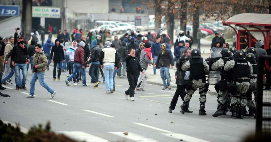 A group of ethnic Albanians throw stones at police during a violent protest in Skopje, Macedonia, on Saturday as they show their support for newly named defense minister Talat Xhaferi, and as a contra-protest to Macedonian protests overnight Friday when scuffles broke out with police.  A series of scuffles erupted late on Friday and continued over night when a group of a few hundred Macedonians started protesting against the designation of the new defense minister Talat Xhaferi, an ethnic Albanian and former rebel commander. Photo: AP
