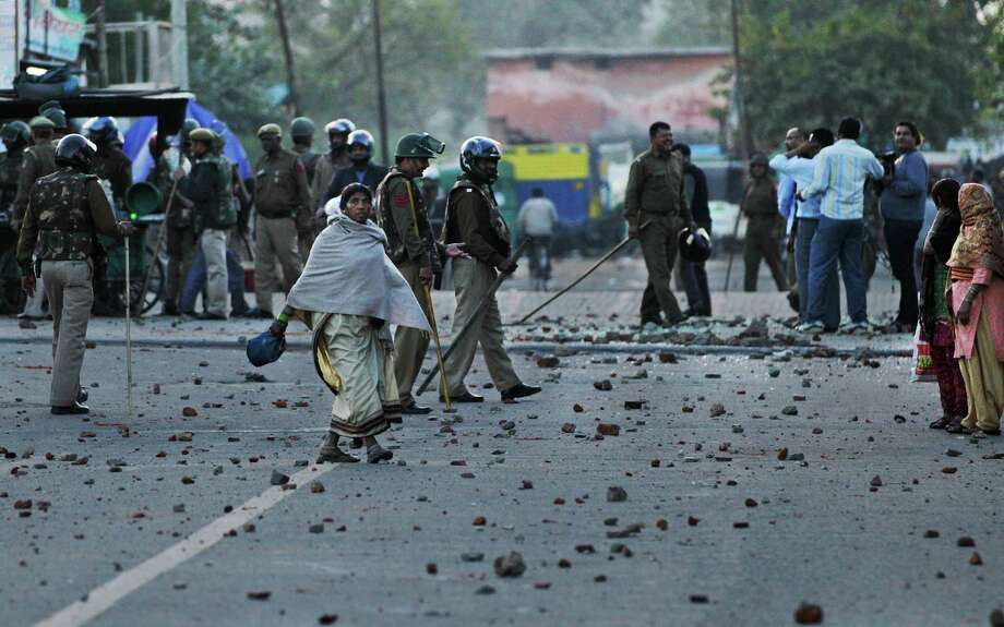 An Indian woman walks past Delhi policemen standing guard on a road scattered with shattered glass and stones  during a protest against the rape of a 7-year-old girl in New Delhi, India, Friday. Police are investigating the rape inside a state-run school in the Indian capital. Angry mobs gathered at the hospital and threw stones at a nearby bus, shattering its windows. Police cordoned off the road and were trying to disperse the crowd. Photo: AP