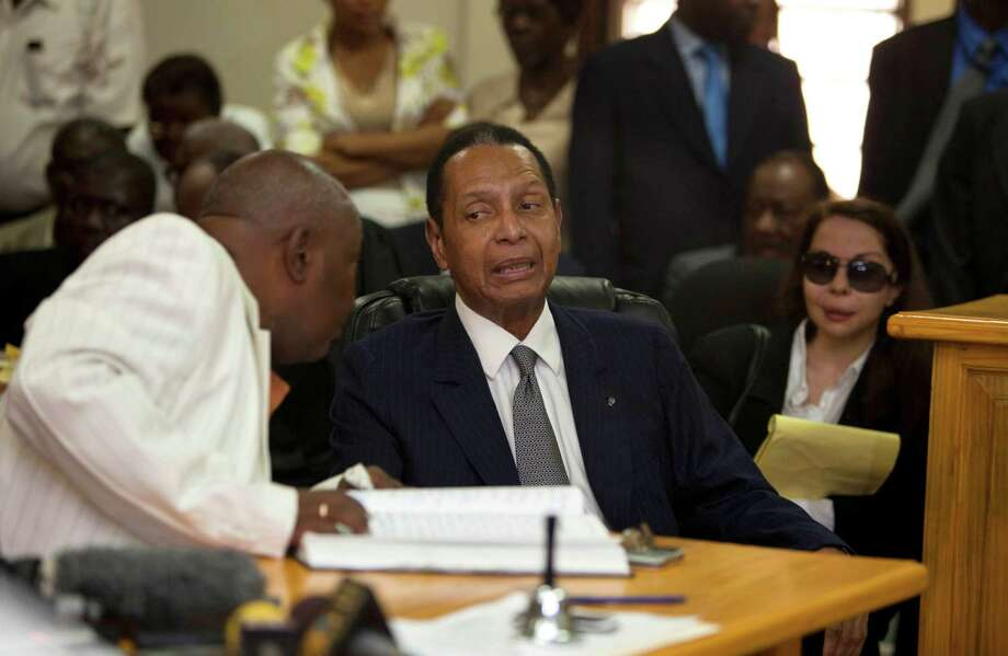"Former Haitian dictator Jean-Claude Duvalier, known as ""Baby Doc,"" center, attends his hearing as his companion Veronique Roy sits behind, right, inside a courthouse in Port-au-Prince, Haiti, Thursday. Duvalier appeared in court Thursday after three times shunning a summons for a hearing on whether he should be charged with human rights abuses during his brutal 1971-1986 regime. Next to him sat his defense attorneys and his longtime partner, who did not remove her sunglasses during the proceedings. Photo: AP"