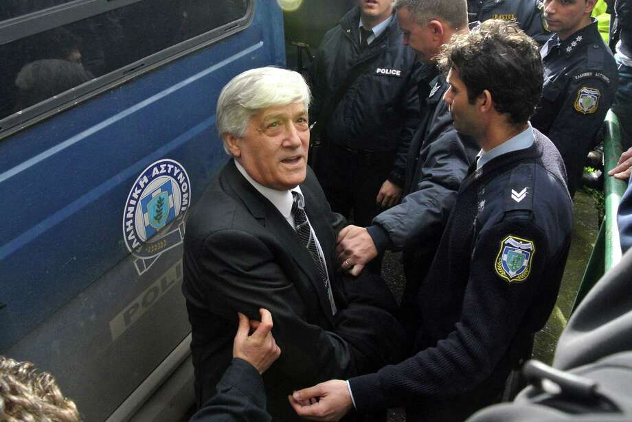 The municipality's former general secretary, Mihalis Lemousias, is escorted by police officers to a police van in Thessaloniki on Wednesday. A court in the northern Greek city of Thessaloniki has convicted three of the city's former top officials, including a former mayor, and sentenced them to life imprisonment for embezzling more than euro 17 million from the municipality. Photo: AP