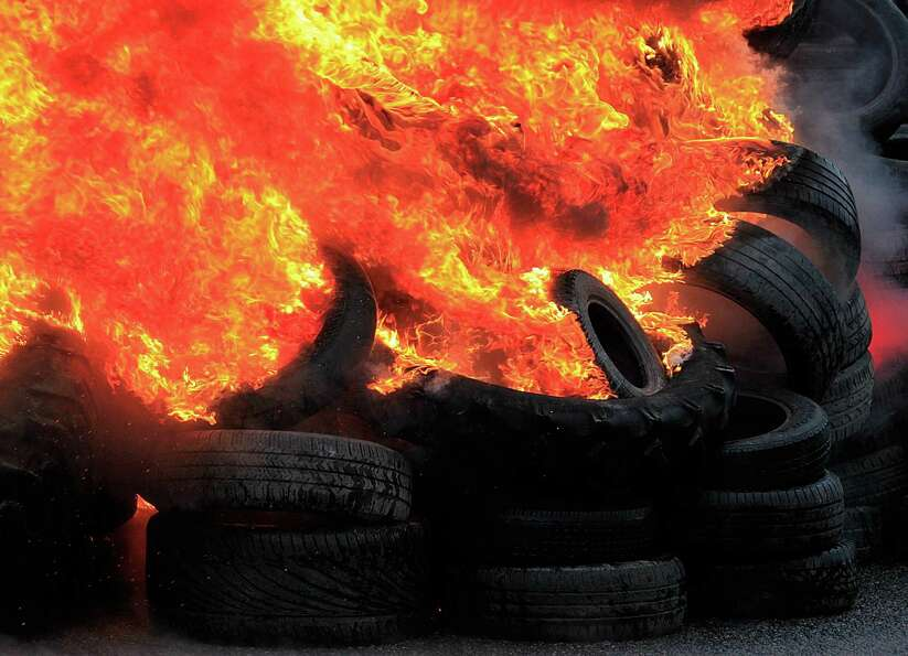 Goodyear employees gather around burning tires, outside the Goodyear tire company, in Amiens, northe