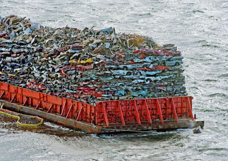 A barge laden with scrap car hulks sits level in the water, anchored near the northern shore of Commencement Bay, Tacoma, Monday.  When the Coast Guard says a barge loaded with crushed Canadian cars can be moved it will finish a trip to a metal recycling yard in Tacoma - minus a few of the cars that splashed into Commencement Bay when the barge started leaking. Photo: AP