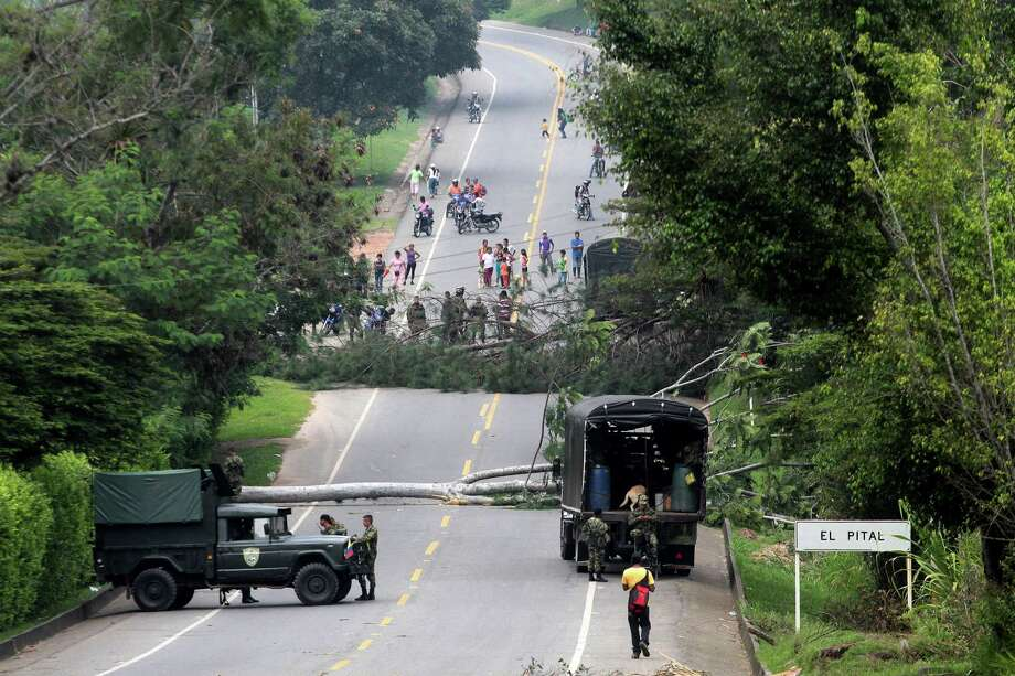 Soldiers guard a roadblock set by small farmers on the Pan American Highway in Piendamo, southern Colombia, Wednesday. Coffee growers across much of the country, blocked roads on the third day of protests asking government for support against falling prices. Photo: AP