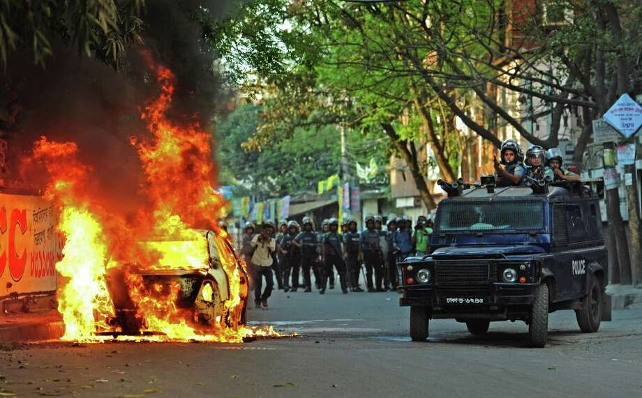 A car stands in flames after activists of the opposition Bangladesh Nationalist Party (BNP) set it on fire during a protest in Dhaka, Bangladesh, Saturday. Demonstrators protesting the death penalty given to Delwar Hossain Sayedee, one of the top leaders of the country's largest Islamic party Jamaat-e-Islami, clashed with Bangladeshi security forces for a third straight day on Saturday, killing two people and injuring about a dozen, police said. Photo: AP