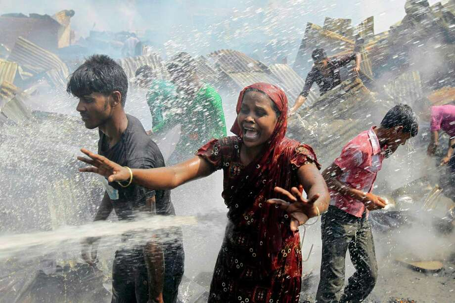 A Bangladeshi woman cries at the scene of a fire at a slum in Dhaka, Bangladesh, Wednesday. According to police, at least 300 shanties were gutted. No casualties were reported. Photo: AP