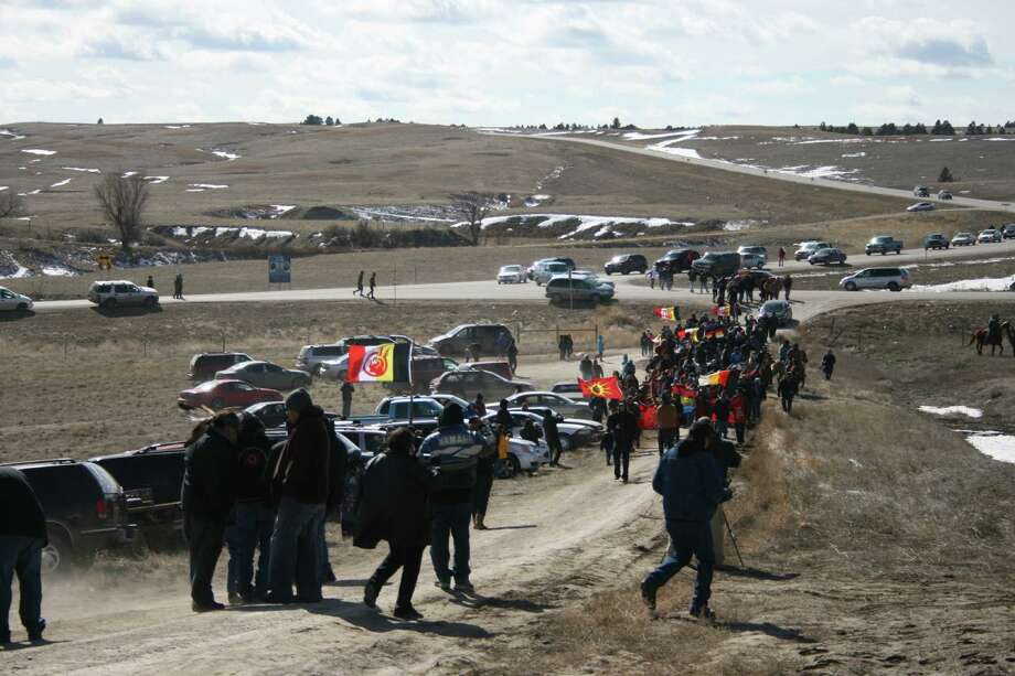 Members of the American Indian Movement walk to the Wounded Knee Massacre Monument Wednesday in Wounded Knee, S.D. Wednesday marked the 40th anniversary of the start of the 71-day occupation in the village of Wounded Knee on the Pine Ridge Indian Reservation. Hundreds of AIM members and other supporters turned out for a day of ceremonies to commemorate the anniversary of the fatal standoff that drew national attention to the impoverished reservation and the plight of local tribes.. Photo: AP