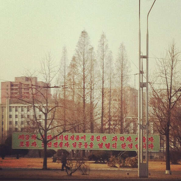 In this photo posted on Instagram, a man walks in Pyongyang, North Korea, under a new roadside banne