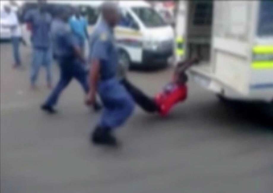 In this still frame from TV and courtesy of South African Daily Sun newspaper, showing a South African man with his hands tethered to the back of a police vehicle being dragged behind as police hold his legs up and the vehicle apparently drives off, east of Johannesburg Tuesday. Photo: AP