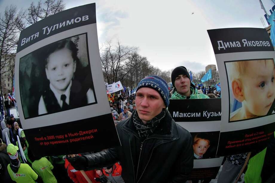 "Demonstrators hold portraits of adopted Russian children who died in U.S., during a massive rally in Moscow, Saturday. Russia voiced strong skepticism Saturday about the U.S. autopsy on Max Shatto, a 3-year-old adopted Russian boy in Texas and demanded further investigation as thousands rallied in Moscow to support the Kremlin ban on U.S. adoptions of Russian children. The poster at left reads: ""Vitya Tulimov died in 2000 in New Jersey at the hands of adoptive parents."" A poster at right reads ""Dima Yakovlev."" Photo: AP"