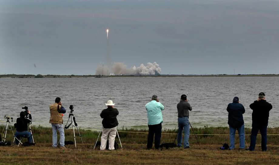 People photograph the Falcon 9 SpaceX rocket as it lifts off from launch complex 40 at the Cape Canaveral Air Force Station in Cape Canaveral, Fla. on Friday. The rocket is transporting the Dragon capsule to the International Space Station containing more than a ton of food, tools, computer hardware and science experiments. Photo: AP