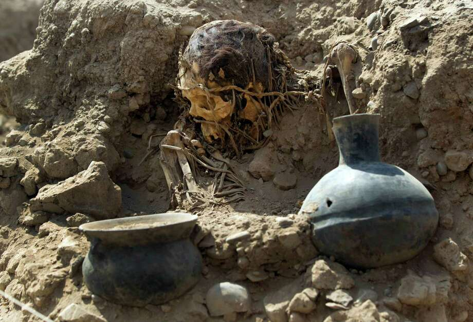 An excavated skull and artifacts lay unearthed at the sports complex where Peru's national soccer team practices in Lima, Peru, Tuesday. According to Peru's Ministry of Culture, 11 pre-Inca tombs belonging to the Lima culture (200-700 AD) and Yschma (1100-1400 AD) were located inside the sports complex in the district of San Luis, where excavations started in Dec. 2012. Photo: AP