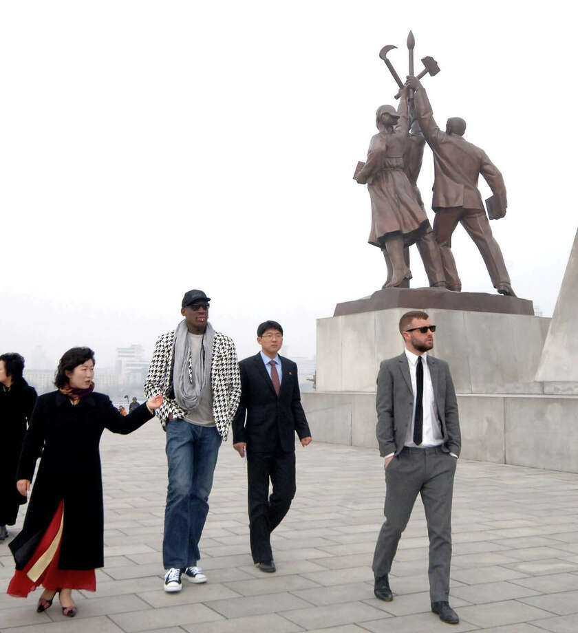 "In this image released by the Korean Central News Agency (KCNA) and distributed by the Korea News Service, former NBA star Dennis Rodman, third right, walks by the base of the Tower of the Juche Idea in Pyongyang in North Korea on Friday.  Ending his unexpected round of basketball diplomacy in North Korea on Friday, ex-NBA star  Rodman called leader Kim Jong Un an ""awesome guy"" and said his father and grandfather were ""great leaders."" (AP Photo/KCNA via KNS)  Photo: AP"