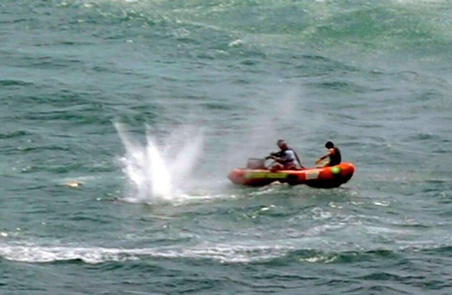 Police in inflatable rubber boats shoot at a shark off Muriwai Beach near Auckland, New Zealand, Wed