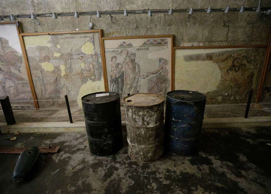 Fuel barrels are stored Tuesday in front of Roman and Byzantine mosaics inside the 17th-century caravanserai, which presently serves as a headquarters for the Free Syrian Army, in Maaret al-Numan, Idlib province, Syria.  Photo: AP