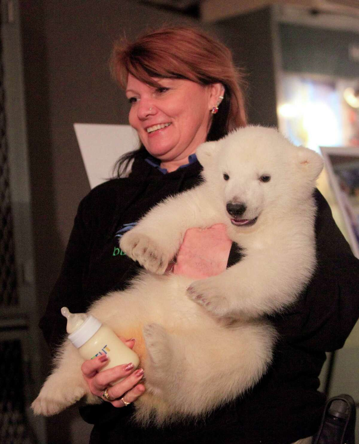 Veterinary technician Alice Rohauer holds a three-month-old polar bear as she is introduced to the public during an event to launch the