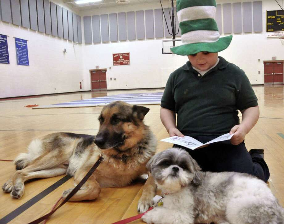 Nicholas Stewart, a second-grader at Heights-Terrace Elementary/Middle School in Hazleton, PA, reads a book to Ekko, a six-year-old German shepherd and Buttons, a two-year-old Shih Tzu, during a Read Across America celebration Friday honoring Dr. Seuss'  birthday. Both dogs serve as therapy and are handled by Lydia Latella. Photo: AP