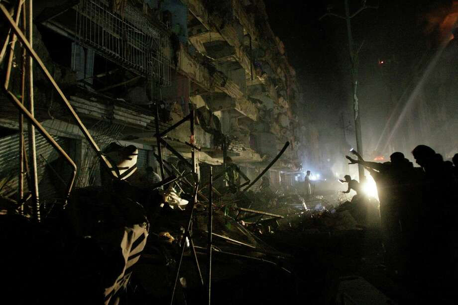 Pakistanis check the site of a bomb blast in Karachi, Pakistan, Sunday. Pakistani officials say a bomb blast has killed dozens of people in a neighborhood dominated by Shiite Muslims in the southern city of Karachi. Photo: AP