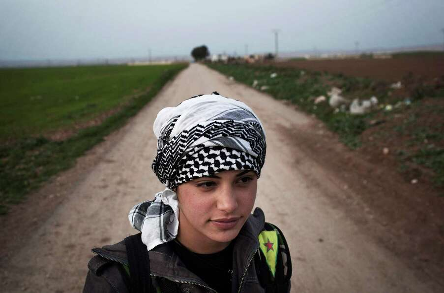 A Kurdish female member of the Popular Protection Units stands guard at a check point near the north