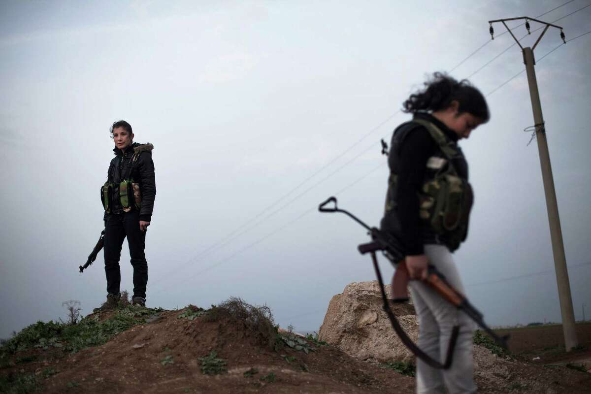 Kurdish female members of the Popular Protection Units stand guard at a check point near the northeastern city of Qamishli, Syria, Sunday.