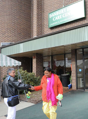 Danbury Health Care Center C.N.A. Manny Ramirez, of Danbury, Conn., enters work, shaking hands with C.N.A. Marie Obas, of Danbury, Conn., who just finshed her shift at the Danbury Health Care Center in Danbury, Conn. Sunday, March 3, 2013.  Employees have been on strike with the New England Health Care Employees Union District 1199 since July and Sunday was their first day back at work. Photo: Tyler Sizemore / The News-Times