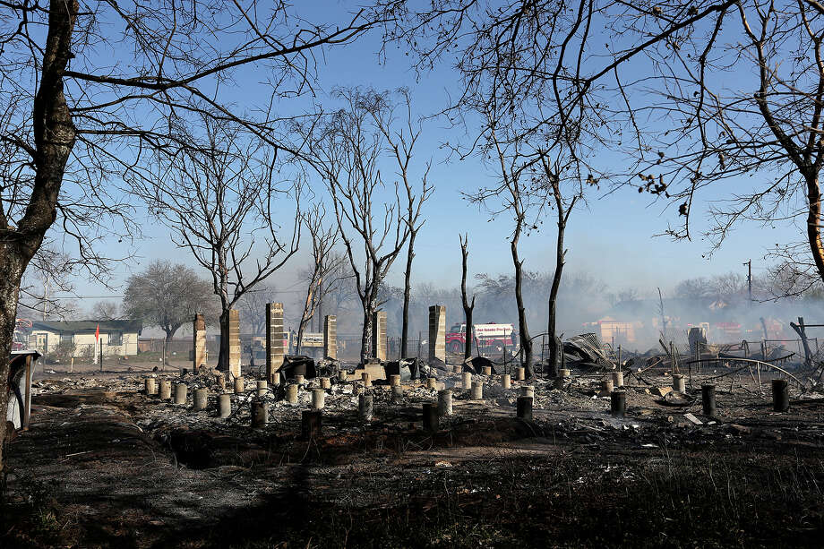 Concrete piers and support columns are all that is left of a house as emergency personnel battle a multi-structure fire at the 8100 block of Old Pearsall Road, Monday, Feb. 25, 2013. The fire was fueled by high winds and destroyed five houses. An 83-year-old woman pulled out of one of the houses was transported to a local hospital in unknown condition. Photo: Jerry Lara, San Antonio Express-News / ©2013 San Antonio Express-News