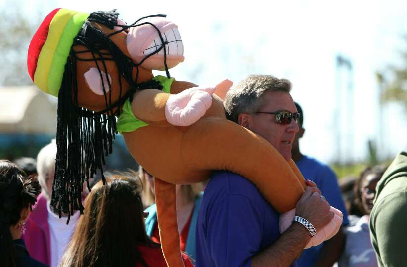 Rick Oria carries the prize he won for his son in the Carnival at the Houston Livestock Show & R