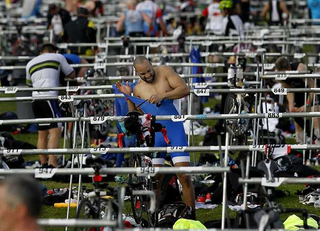 A triathlete struggles with his jersey before the bicycling portion of the Escape From Alcatraz Triathlon, normally held in June. Photo: Brant Ward, The Chronicle