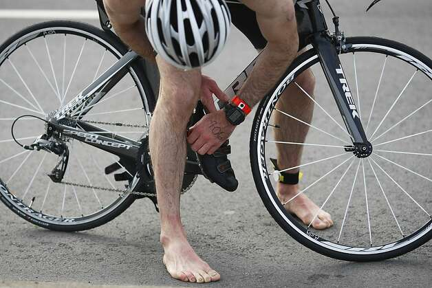 A cyclist struggles with his shoes as he tries to make his way along the bike route on Sunday, March 3.The triathlon featured swimming from Alcatraz to the Marina followed by an 18 mile bike ride and an 8 mile run. Photo: James Tensuan, The Chronicle