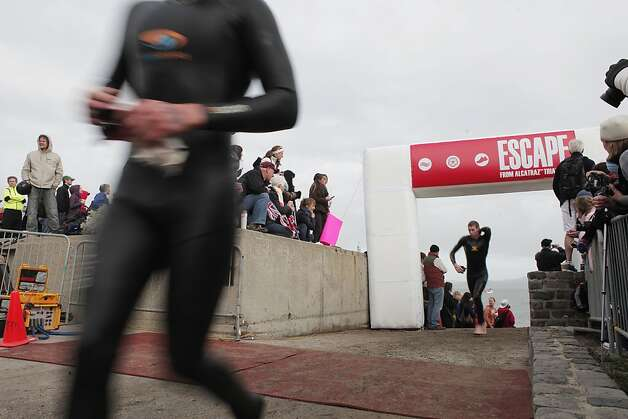 Triathletes exit the beach and make their way to the next portion of the Escape from Alcatraz Triathlon on Sunday, March 3. The triathlon featured swimming from Alcatraz to the Marina followed by an 18 mile bike ride and an 8 mile run. Photo: James Tensuan, The Chronicle