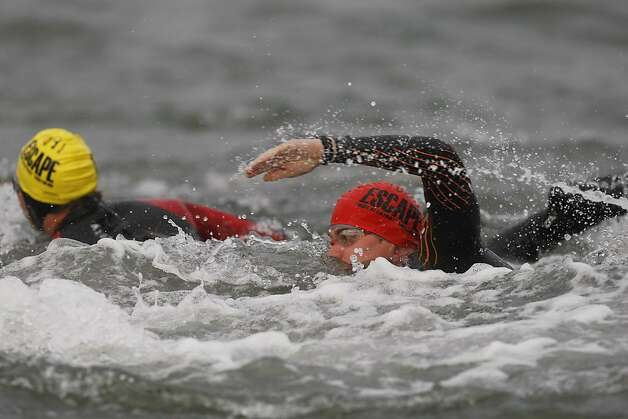 Competitors swim across the bay in Sunday's Escape From Alcatraz Triathlon, in which a man died. Photo: James Tensuan, The Chronicle