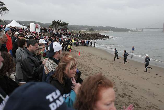 Some of the first triathletes make their way onto the beach during the Escape from Alcatraz Triathlon on Sunday, March 3. The triathlon featured swimming from Alcatraz to the Marina followed by an 18 mile bike ride and an 8 mile run. Photo: James Tensuan, The Chronicle