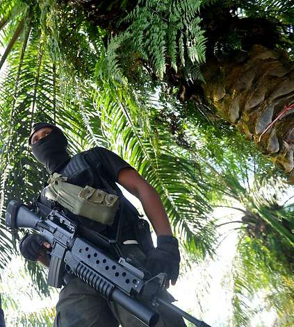 A Malaysian police commando stands guard in Tanduo village in the state of Sabah, the site of a bloody attack. Photo: Associated Press