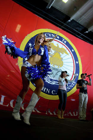 Dallas Cowboy cheerleader Cassie Trammell, left, performs a dance routine as American Idol finalists Diana DeGarmo, middle, and Ace Young perform for Sailors in hangar bay two aboard the Nimitz-class aircraft carrier USS John C. Stennis (CVN 74) during a USO sponsored tour led by Vice Chairman of the Joint Chiefs of Staff Adm. James Winnefeld. John C. Stennis is deployed to the U.S. 5th Fleet area of responsibility conducting maritime security operations, theater security cooperation efforts and support missions for Operation Enduring Freedom. (U.S. Navy photo by Mass Communication Specialist 2nd Class Kenneth Abbate) Photo: MC2 (AW/SW) Kenneth Abbate / DIGITAL