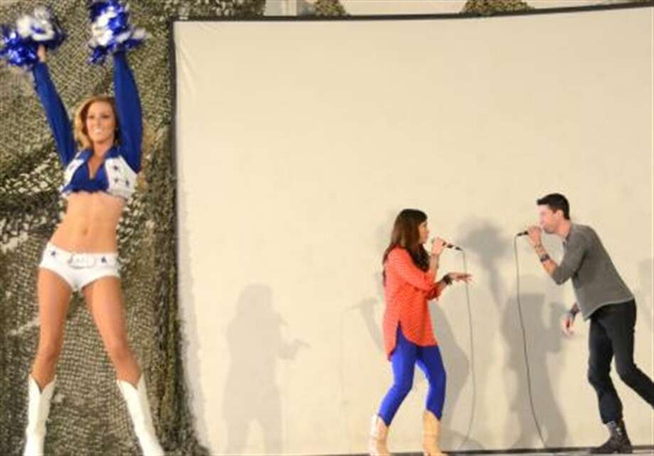 Dallas Cowboy cheerleader Cassie Trammell, left, performs a dance routine as American Idol finalists Diana DeGarmo, middle, and Ace Young perform for Sailors in hangar bay two aboard the Nimitz-class aircraft carrier USS John C. Stennis (CVN 74) during a USO sponsored tour. (Pentagon photo)